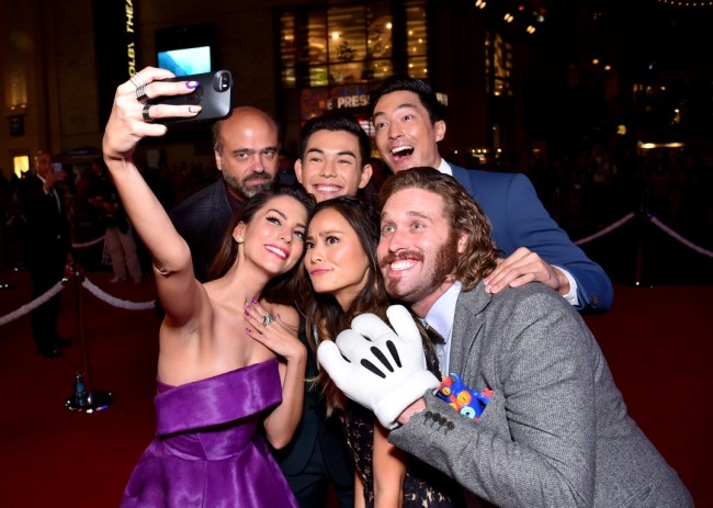 """HOLLYWOOD, CA - NOVEMBER 04:  Actress Genesis Rodriguez (L) takes a selfie with actors (L-R) actors Scott Adsit, Ryan Potter, Jamie Chung, Daniel Henney and T.J. Miller during the Los Angeles Premiere of Walt Disney Animation Studios' """"Big Hero 6"""" at El Capitan Theatre on November 4, 2014 in Hollywood, California.  (Photo by Alberto E. Rodriguez/Getty Images for Disney) *** Local Caption *** Genesis Rodriguez;Scott Adsit;Ryan Potter;Jamie Chung;Daniel Henney;T.J. Miller"""